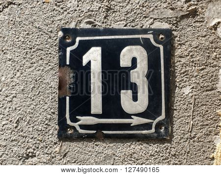 Old retro weathered cast iron plate with number 13