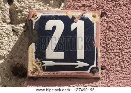 Weathered grunge square metal enameled plate of number of street address with number 21 closeup