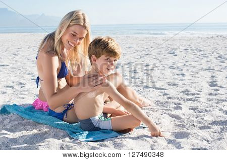 Young mother applying sunscreen lotion on son shoulder. Woman at beach applying suntan lotion on back son and boy looking at camera.