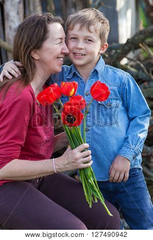 Boy gives red flowers tulips his grandmother on a holiday