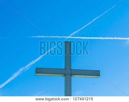 Detail of a religious cross while a cross is designed into the sky by a trail of two airplanes ** Note: Visible grain at 100%, best at smaller sizes