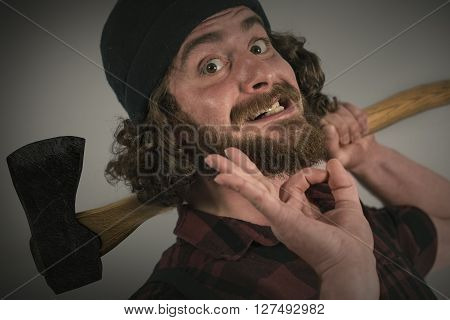Silly hipster lumberjack gives okay sign while holding axe