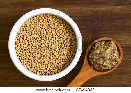 Yellow mustard seeds in bowl and whole grain mustard on wooden spoon photographed overhead on wood with natural light (Selective Focus Focus on the top of the seeds and the mustard)