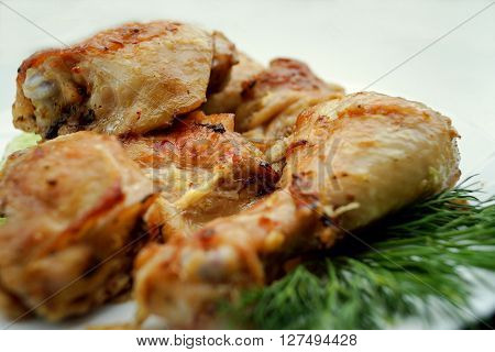 Pieces of fried chicken on a white platedecorated with greens of a parsley.