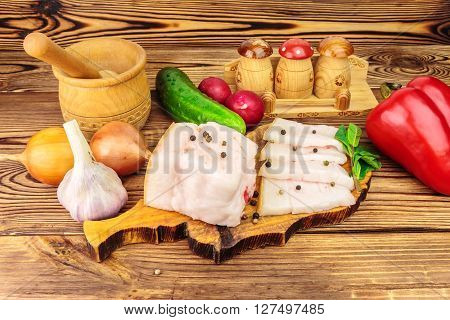 Piece and sliced fresh raw pork lard on wooden board with vegetables spices on the table