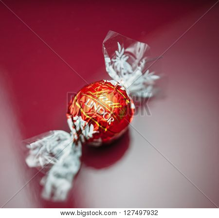KILCHBERG SWITZERLAND - MARCH 20 2014: Lindt Lindor chocolate truffle on a red luxury silk background. Lindt is one one of the lastgest luxury chocolate and confectionery company worldwide with more than 30 factories worldwide