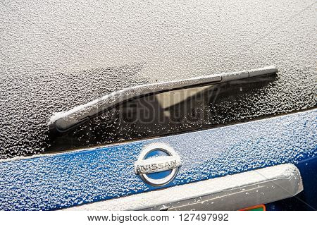 PARIS FRANCE - JAN 20 2016:Nissan Motors logotype covered with snow flakes during cold period on Paris streets
