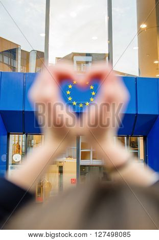 Woman hands in shape of love heart with the stars of European Union in the lhearts shape