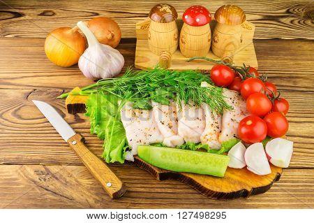 Sliced fresh pork lard fresh produce vegetables on the wooden board and knife on table