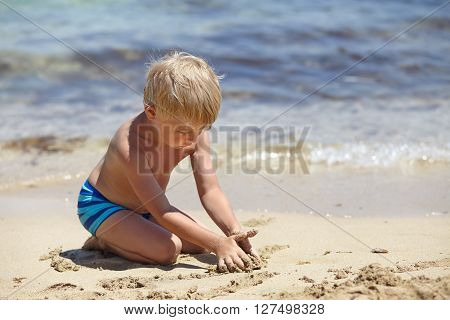 happy kid boy playing on a beach