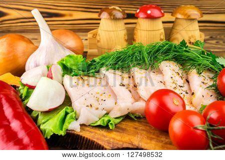 Sliced fresh pork lard fresh produce greens vegetables on the wooden board close-up selective focus