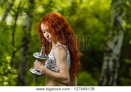 fitness, health, diet concept - stunning beautiful redhead girl with long curly hair and great musculature exercising with heavy dumbbells at summer spring forest