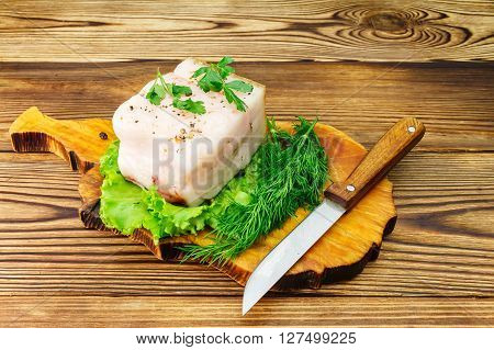Piece and sliced fresh pork lard fresh produce greens on the wooden board and knife on table