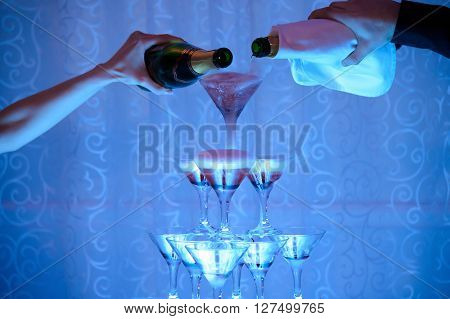 Hands men and women pour champagne into the slide of the glasses. Festive alcohol at the Banquet. Restaurant design wine. Pyramid of champagne.