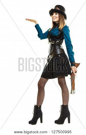 Smiling young steampunk islolated girl on white holding fancy rifle with open hand plam. Fantasy old fashion wearing hat and goggle.