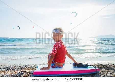 Happy Surfing boy on a beach looking on the sea and ready to go into the water. Sunset time.