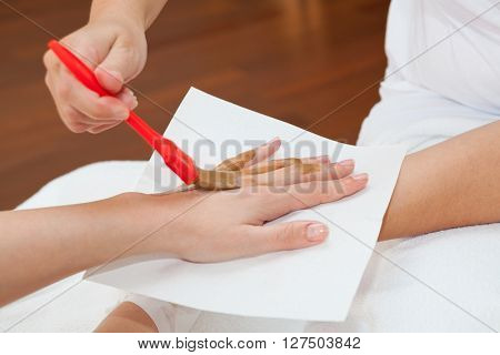 Therapist applying nourishing mask on woman's hand