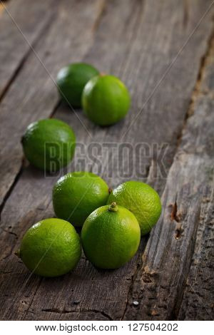 Close-up of bright fresh limes on wooden table