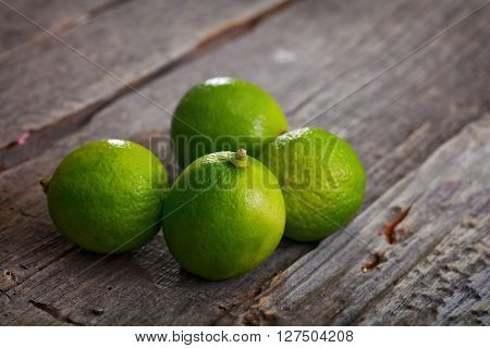 Close-up of four fresh limes on wooden table