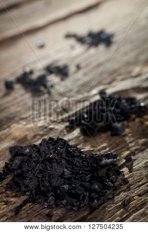 Black salt on wooden table in close-up