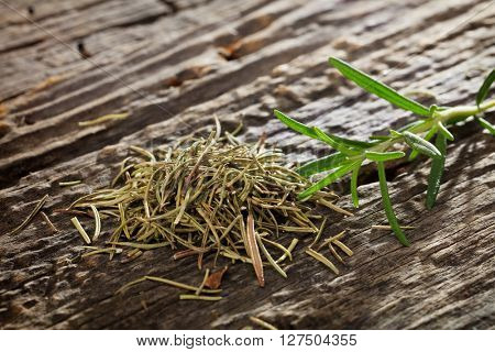 Heap of dry rosemary with fresh one onn wooden table in close-up