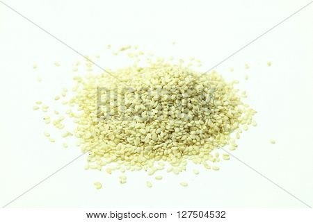 Close-up of sesame seeds in pile on white background