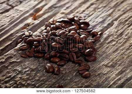 Close-up of pile of brown coffee beans on wooden table