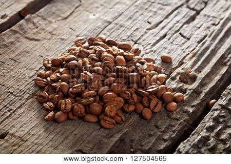 Pile of raw brown coffee beans on wooden table