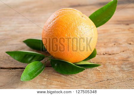 Orange Fruit With Leaves On Wooden Background
