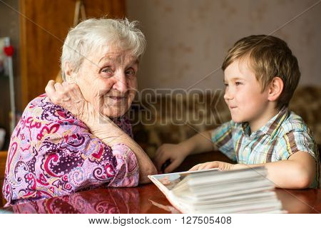Happy grandma sits with his young grandson.