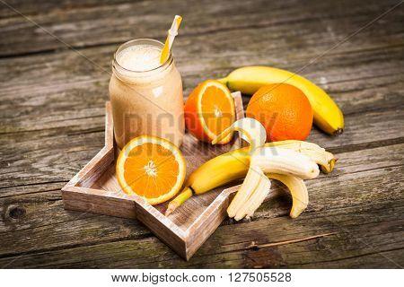Banana orange milkshake on wooden table