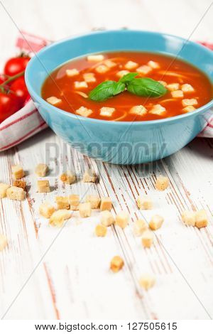 Tomato soup with croutons and basil on wooden table