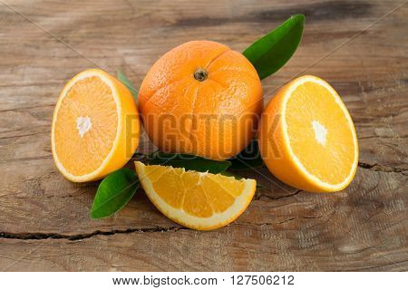 Oranges Fruit With Leaves On Wooden Background