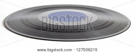 Black vinyl record isolated on white background. In the middle of the center of an empty space for a label with the name of the inscription.