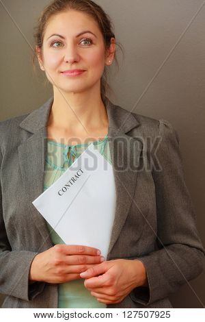 Contracts and agreements concept. Adult beauty woman in jacket holding contract. Close up portrait of person with agreement.