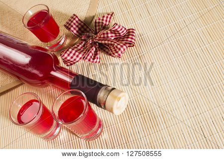 Still life with red alcoholic drink in bottle and glasses on natural background.