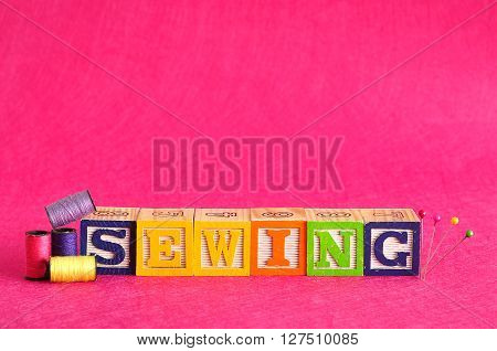 The word sewing spelled with colorful alphabet blocks displayed with spools of thread against a pink background