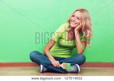 Happy woman with paint brush sitting near painted wall