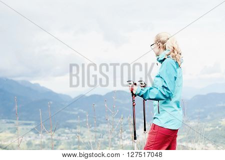 Woman wearing glasses and outdoor clothing (hardshell waterproof jacket and softshell pants), standing with trekking poles in hands during hiking track in Bavarian Alps - healthy lifestyle concept