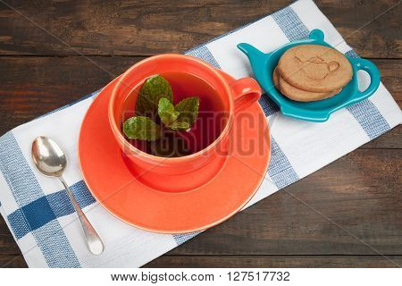 Orange Teacup And Saucer With Cookies And Spoon