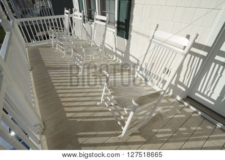 A row of four used and weathered white painted wooden rocking chairs on an elevated dirty porch at sunrise on a sunny day.