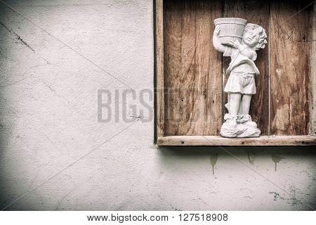 child statue in a garden is carriyng a tray.