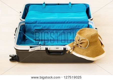 Large family polycarbonate luggage and summer sunny wicker hat on white wooden background.