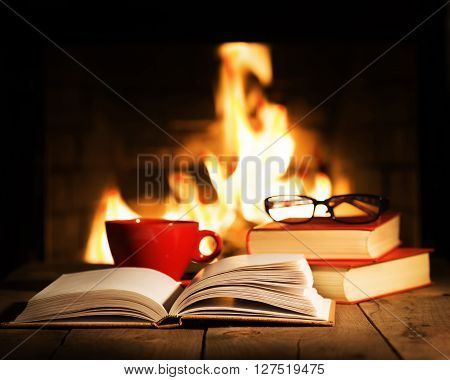 Red Cup And Old Books On Wooden Table Near Fireplace.