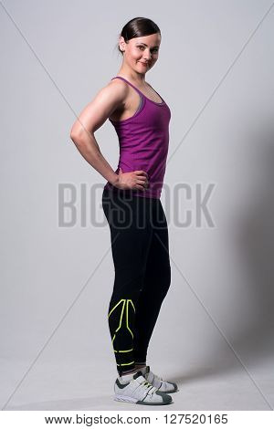 Portrait of athletic brunette. Woman Fitness in full growth on a light background