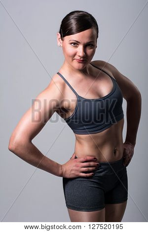 Portrait of athletic brunette. Fitness woman on a light background