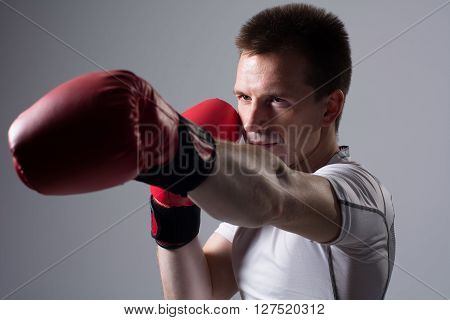 Close-up portrait of boxer in red boxing gloves on a gray background.