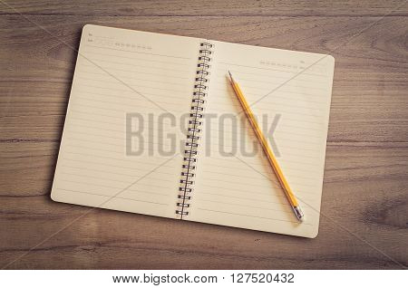 Open Notebook And Pencil On Wood Background