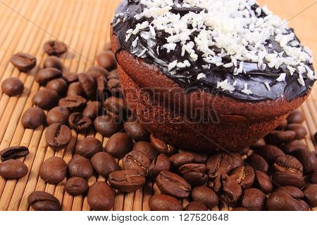 Homemade delicious fresh baked chocolate muffins with desiccated coconut and coffee grains on wooden background concept for dessert