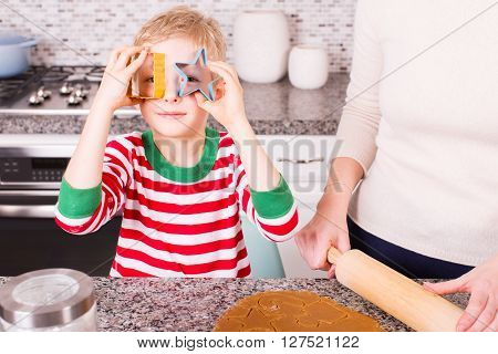 little positive boy in cozy pajamas making gingerbread cookies at home at christmas time and being playful and silly looking through cookies cutters
